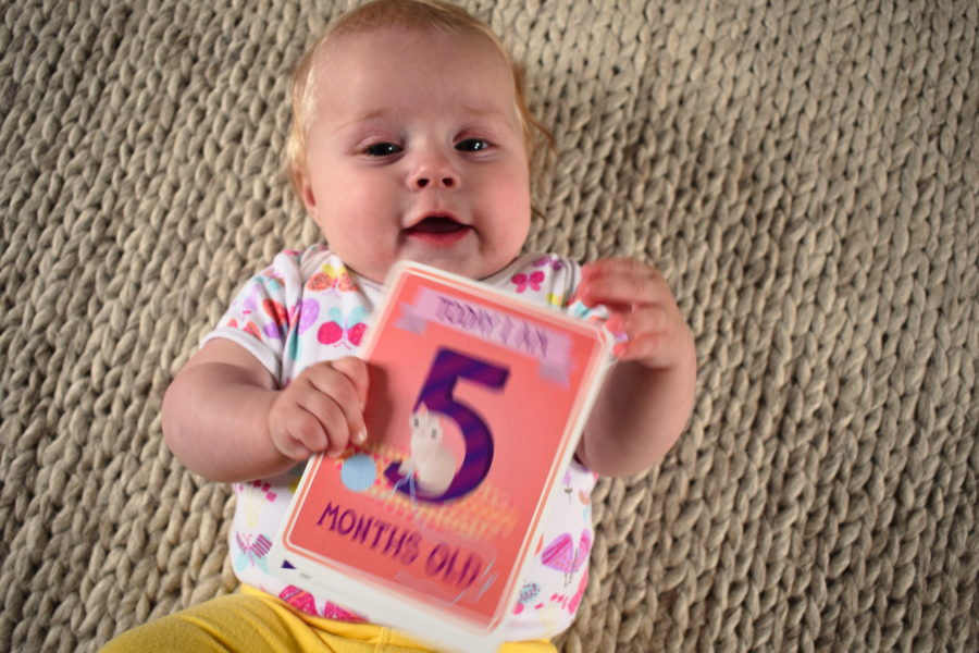 Baby lying on a rug, holding a card which says 'Today I am five months old'