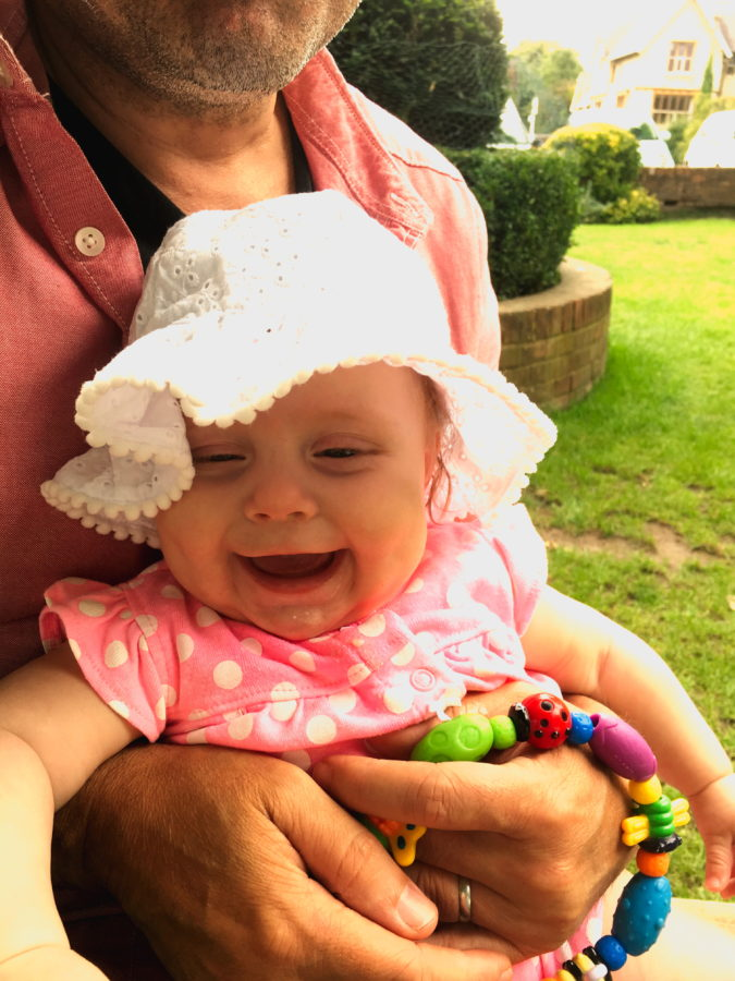 Baby sitting on someone's lap, with a sunhat on, with grass in the background, laughing