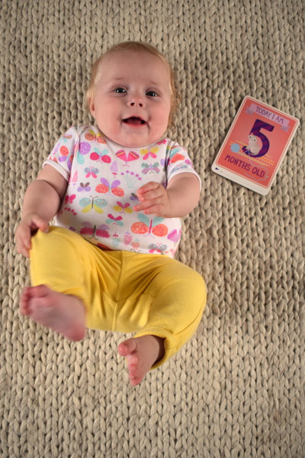 Baby lying on her back with her feet in the air with a card next to her saying 'I am five months old'