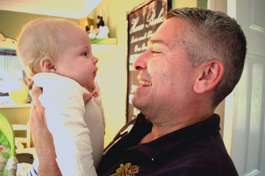 Father holding baby up to face him, smiling and talking to one another