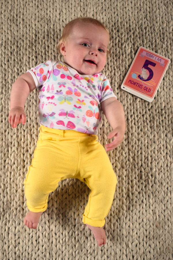 Baby in yellow trousers, lying on the floor with a card next to her which reads 'Today I am five months old'
