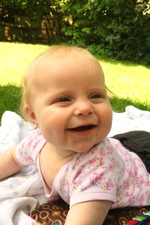 Baby lying on her tummy on a rug on the grass, smiling