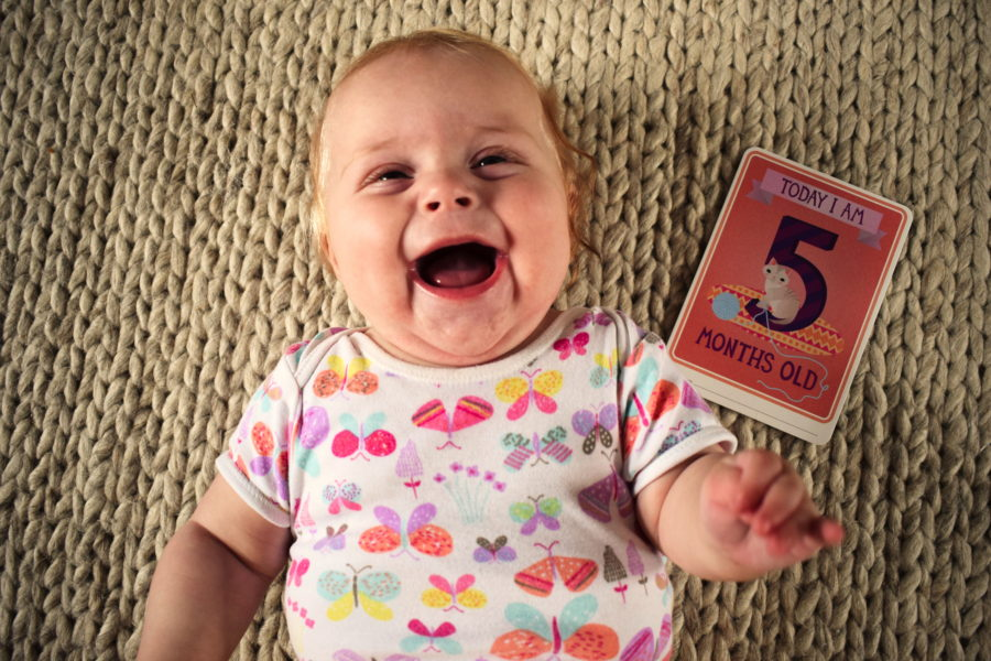 Baby lying on her back, open mouthed laughing, with a card next to her saying 'Today I am five months old'