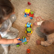 two children under two years old playing with wooden train on the floor