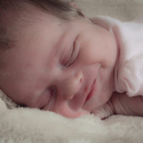 newborn baby asleep on tummy, smiling