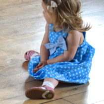 Little girl in blue polka dot party dress and pink shoes, sitting on the floor, looking to the right