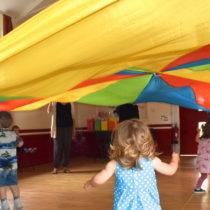 toddlers playing under a brightly coloured parachute at a rainbow party