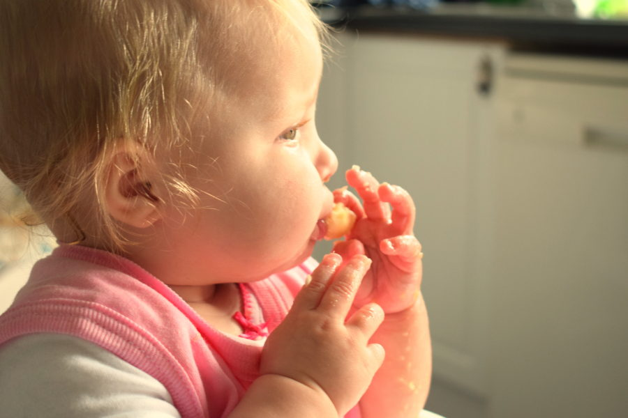 Side profile of baby covered in banana in  pink bib, eating a piece of banana