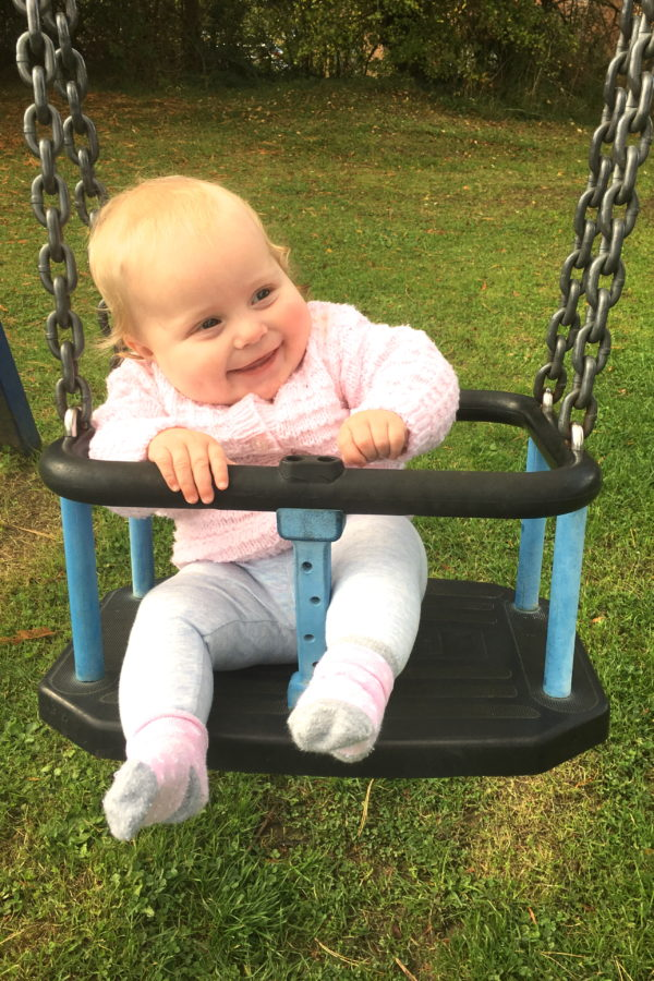 baby sitting on a swing, laughing