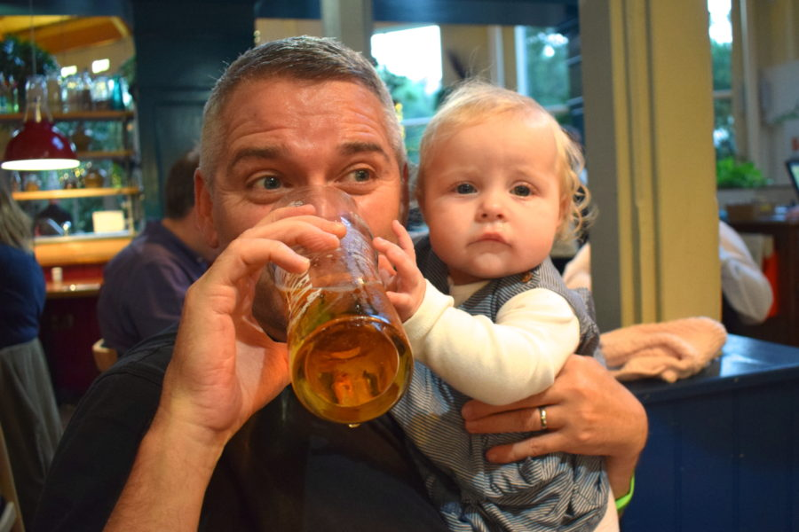 father holding baby girl, drinking from a pint of beer, with baby holding on to the glass