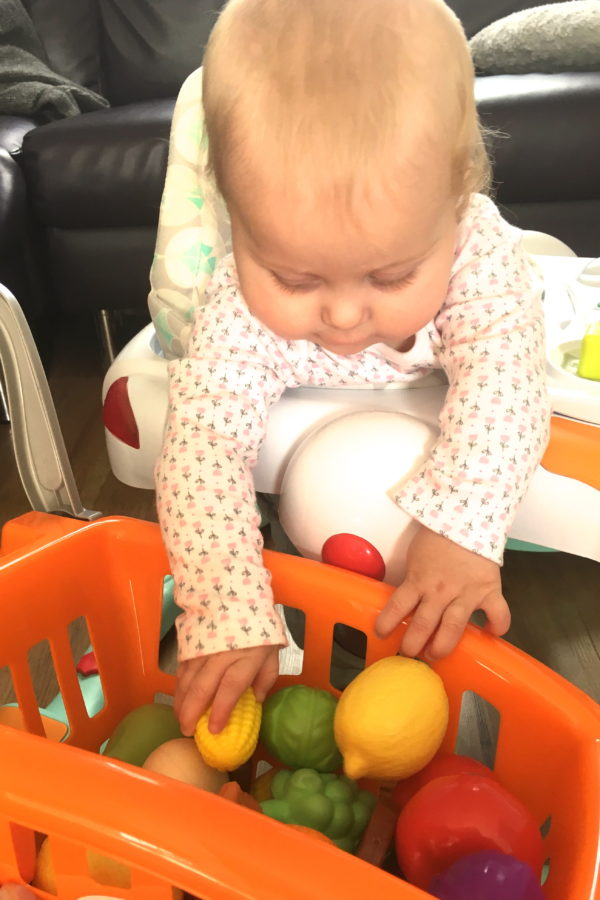 baby leaning out of walker, playing with trolley of plastic fruit and veg