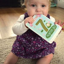 Baby girl sitting up, chewing age milestone card for seven months old