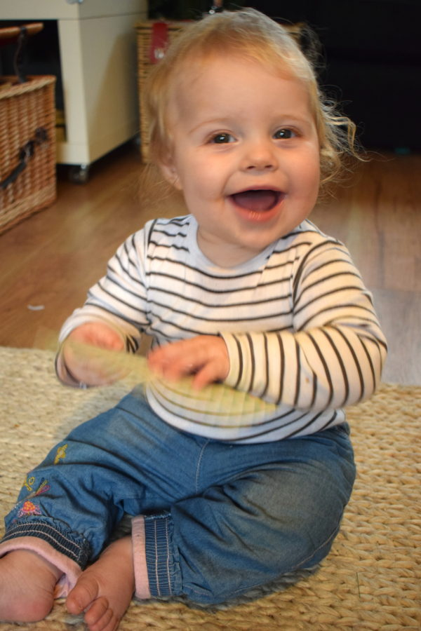 nine month old baby girl in stripy top and jeans, holding a card and laughing