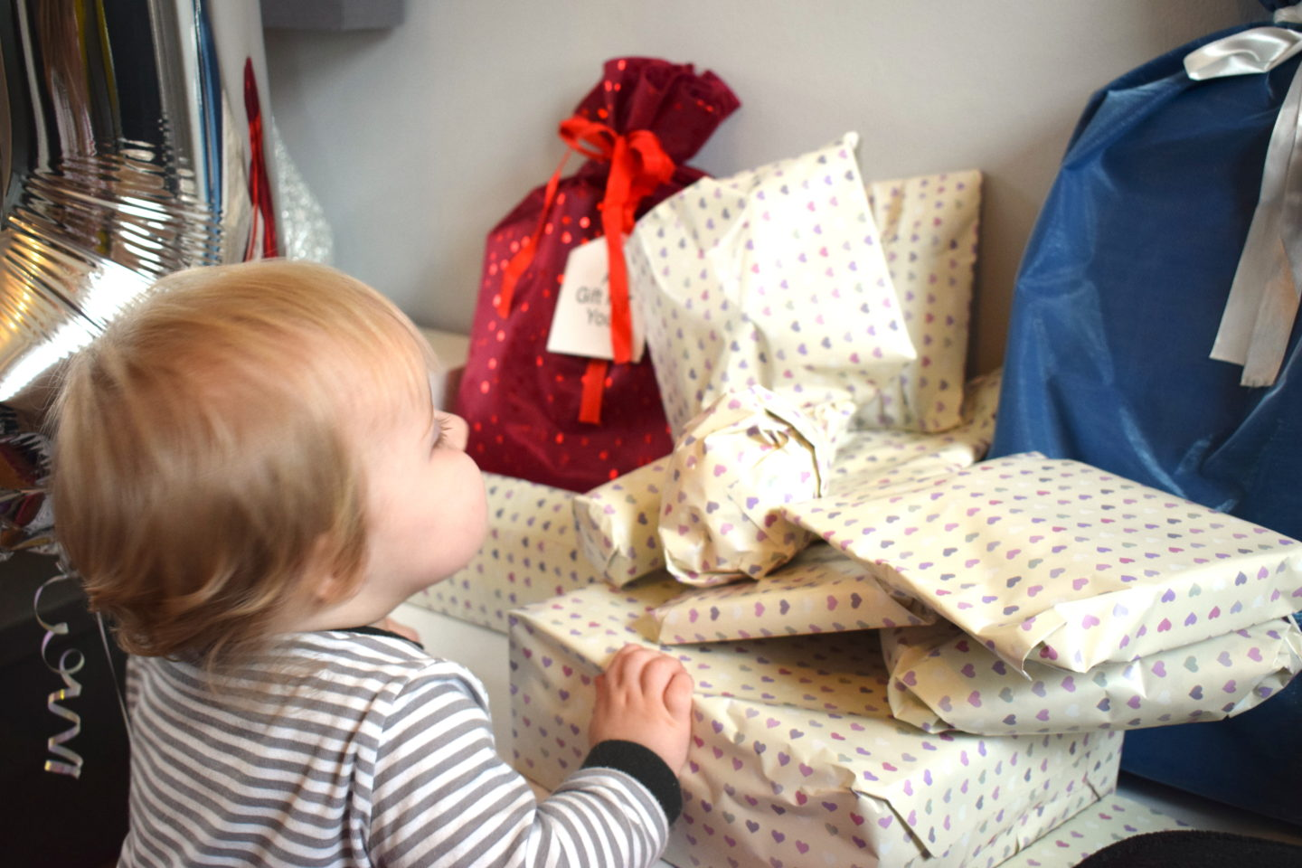 one year old girl, looking at pile of birthday presents