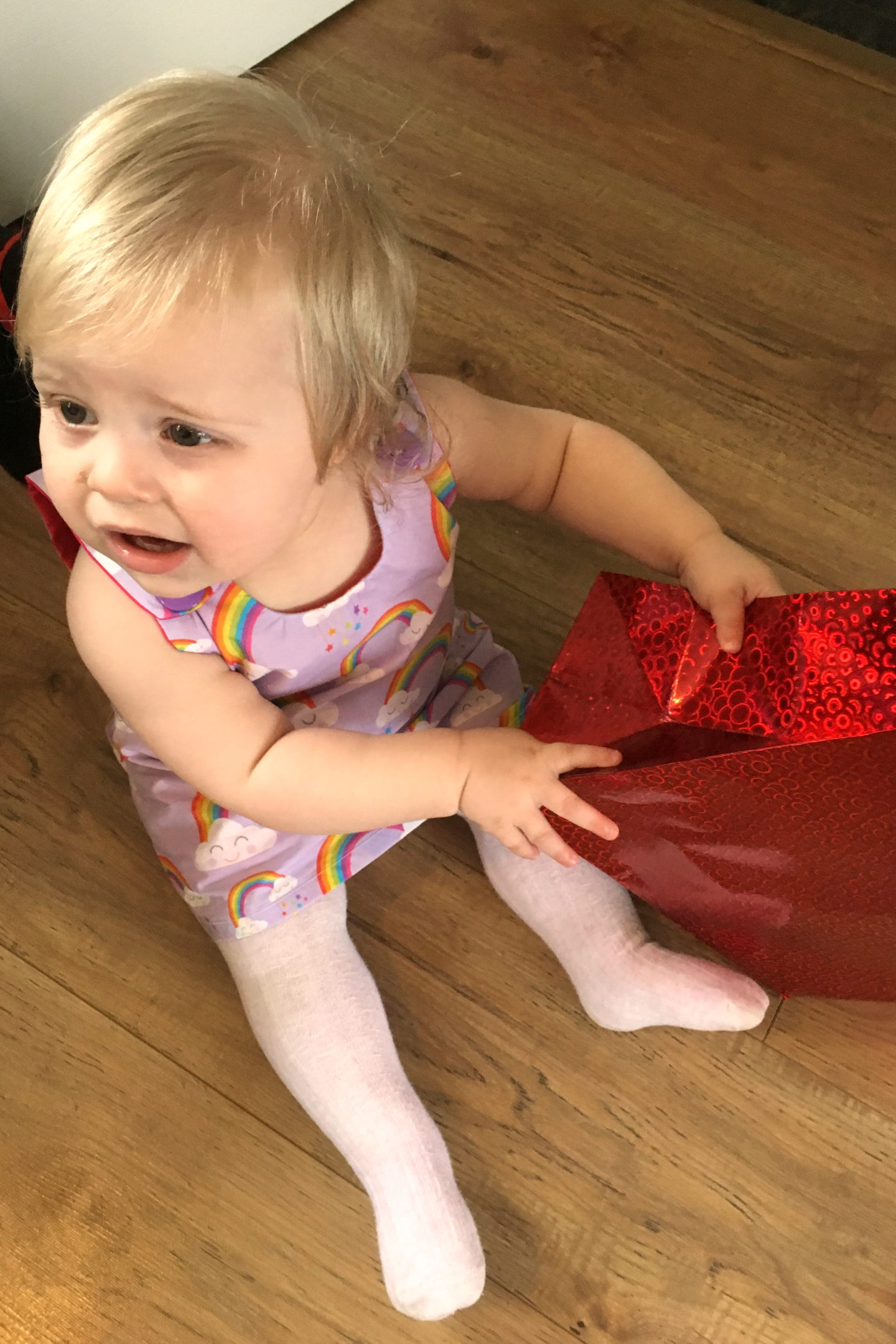 one year old in party dress sitting on the floor holding red gift bag