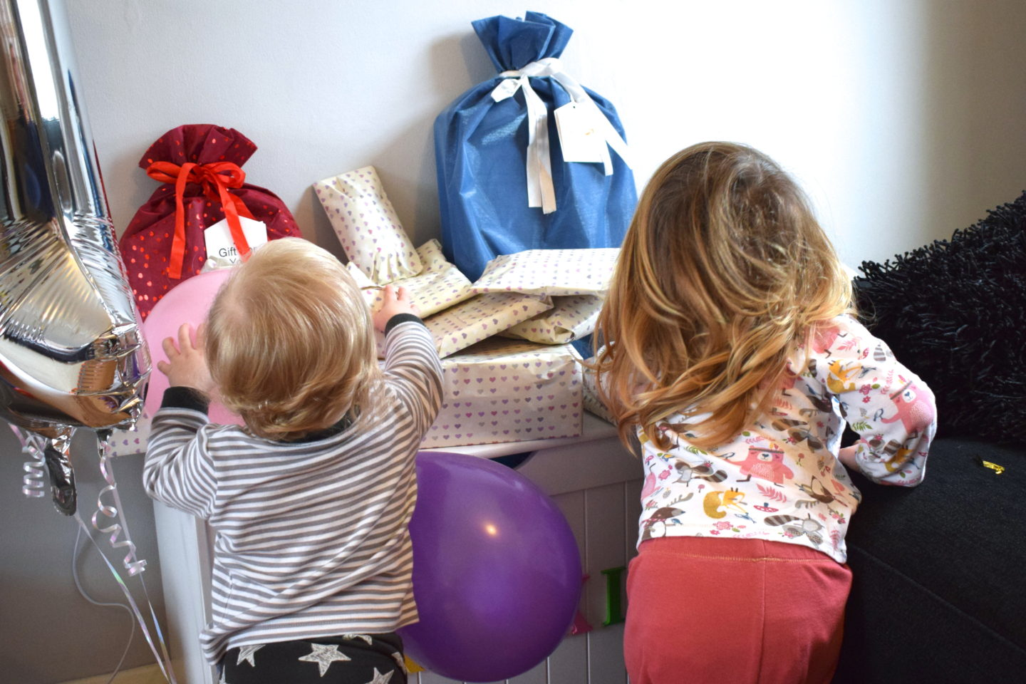 one year old girls with older sister with back to camera, looking at pile of birthday presents