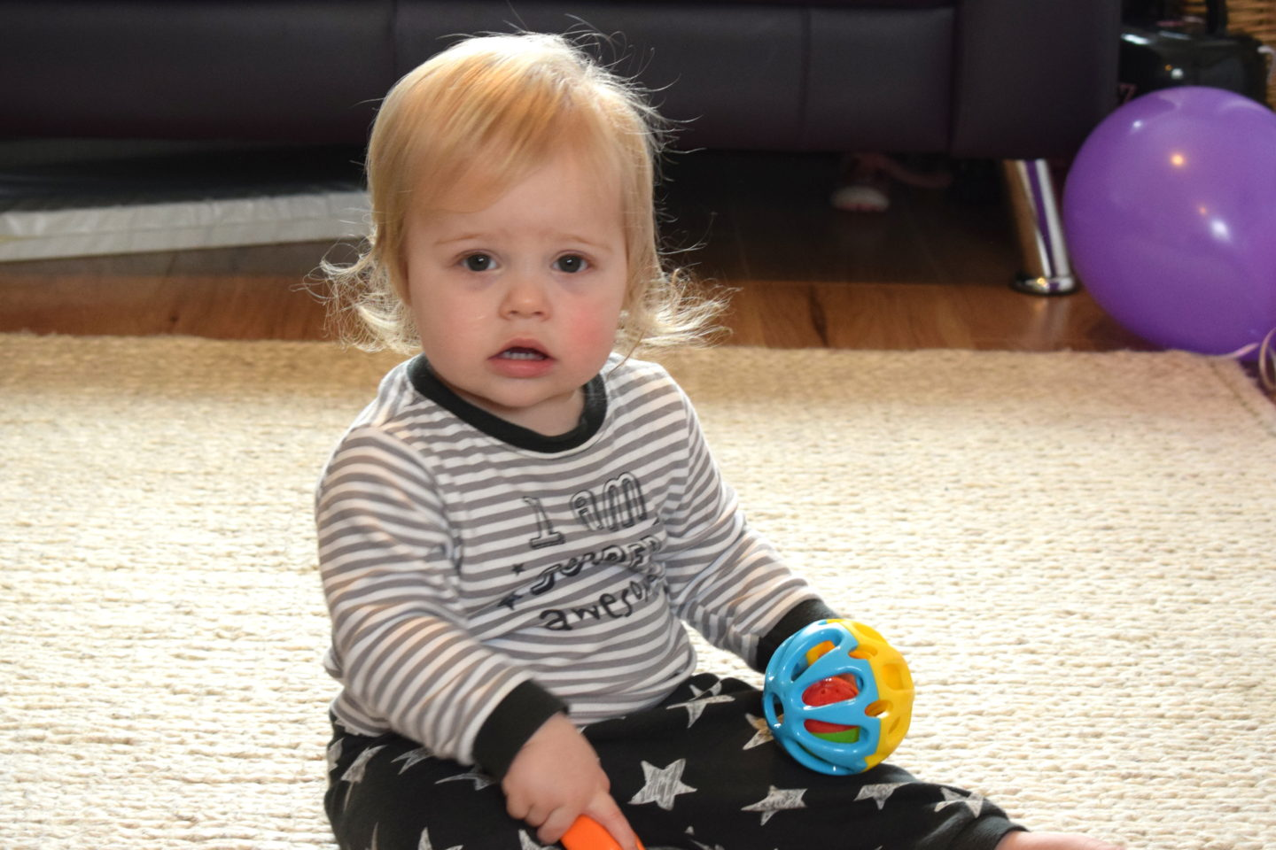 one year old girl in pyjamas, sitting on a rug, holding a ball