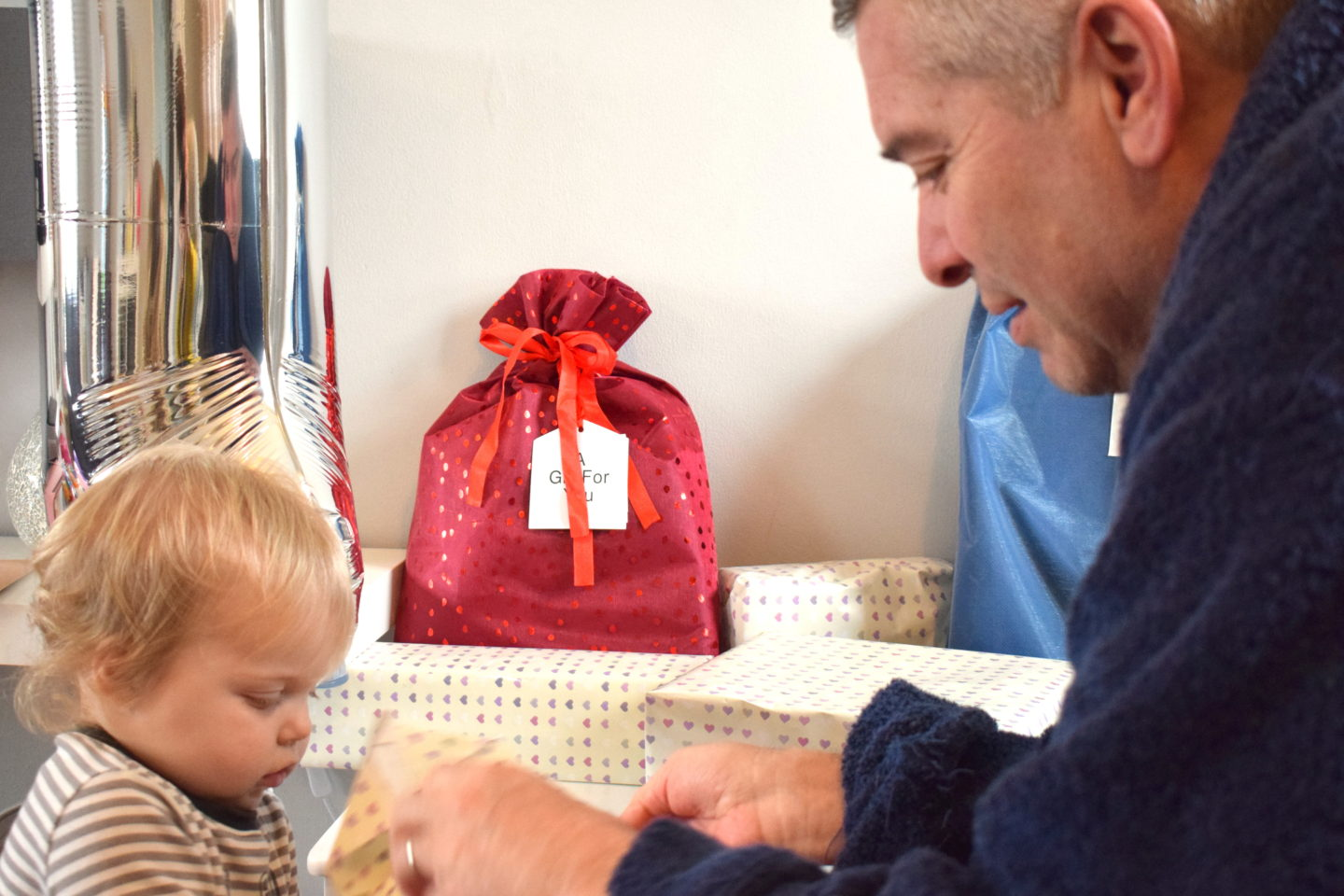 one year old girl standing with dad, opening birthday present