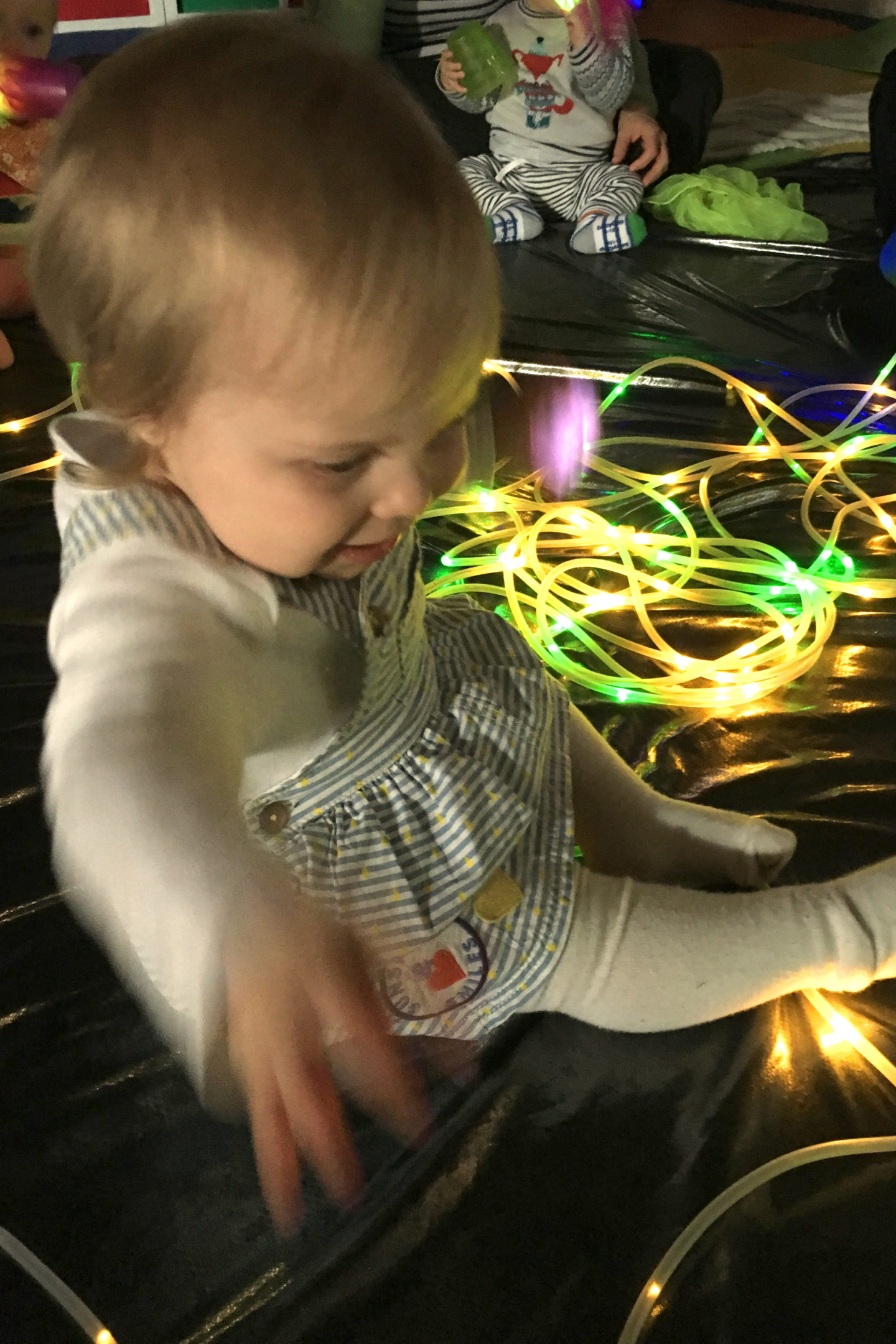 one year old girl in blue dress, playing with string lights, sitting on the floor