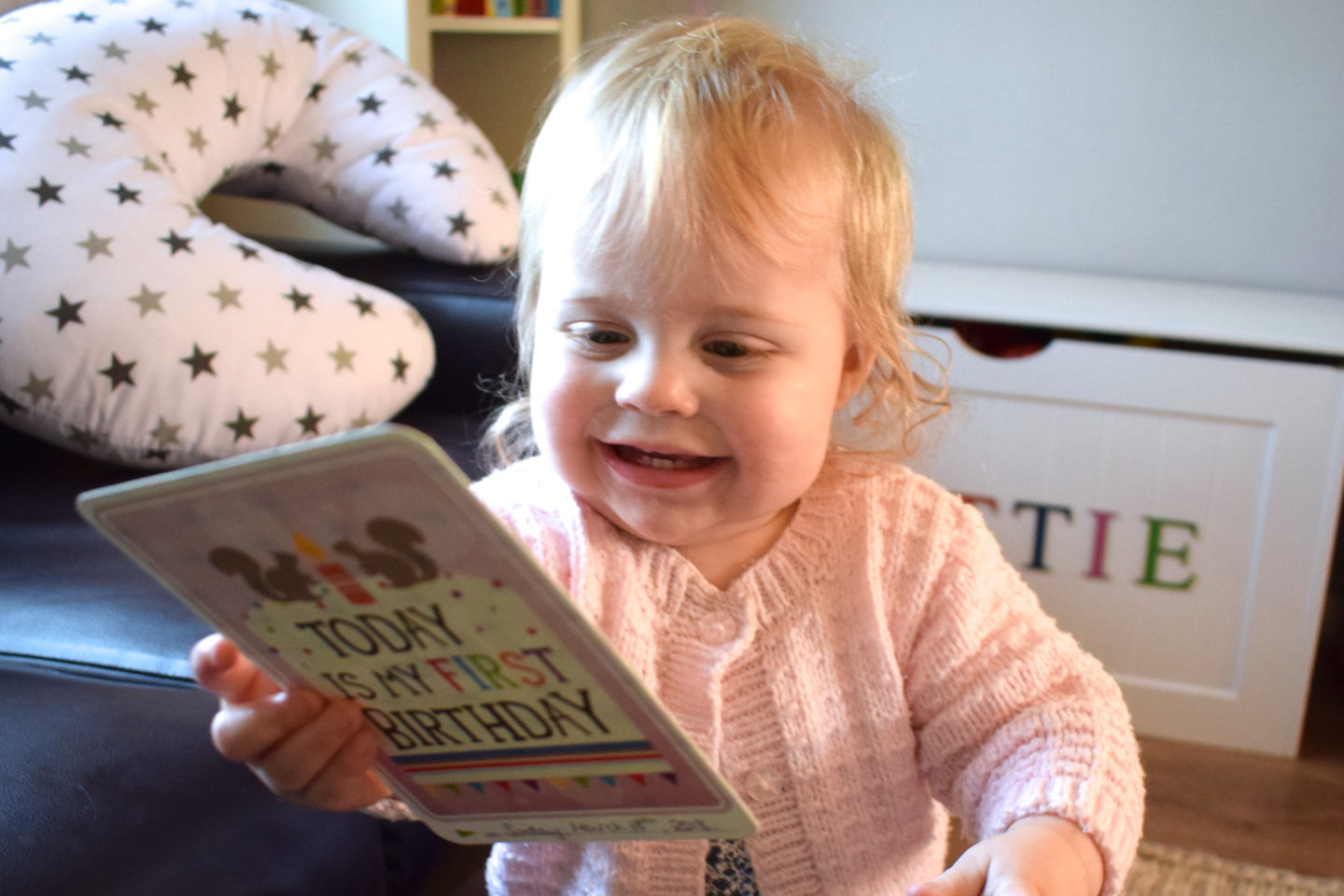 one year old girl in pink cardigan, smiling, holding milestone card saying today is my first birthday