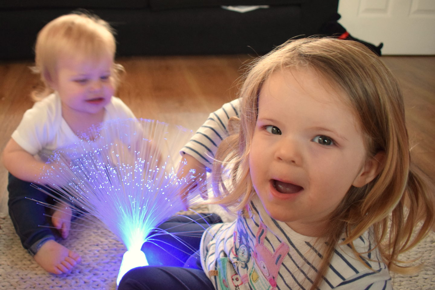 sisters playing with fibre optic lamp and laughing