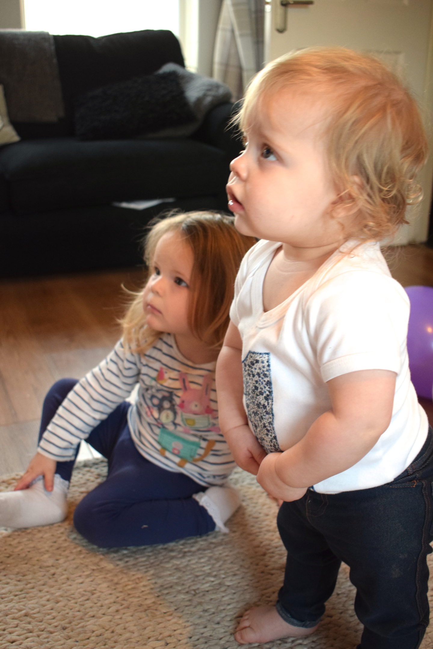 sisters, one standing, one sitting on the floor, watching TV