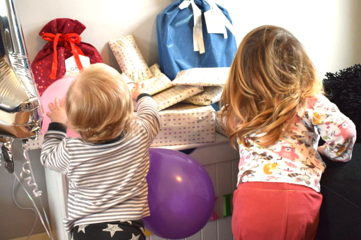 sisters standing next to each other, backs to camera, looking at a pile of birthday gifts